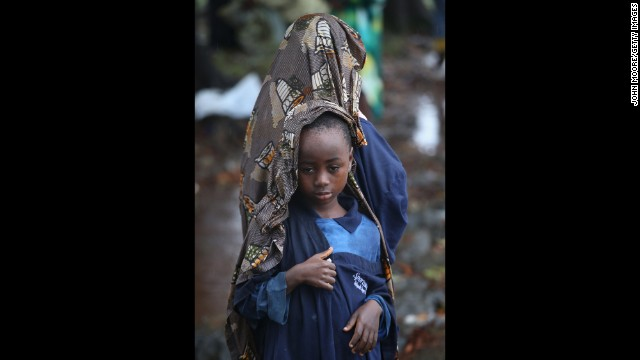 lija Siafa, 6, stands in the rain with his 10-year-old sister, Josephine, while waiting outside Doctors Without Borders' Ebola treatment center in Monrovia on August 17. The newly built facility will initially have 120 beds, making it the largest-ever facility for Ebola treatment and isolation.