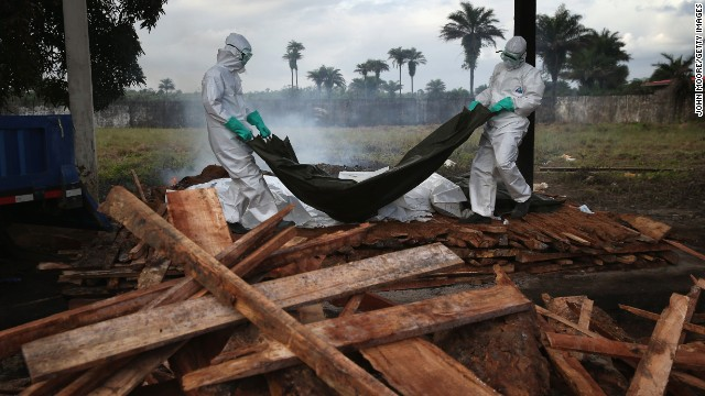 A burial team from the Liberian Ministry of Health unloads bodies of Ebola victims onto a funeral pyre at a crematorium in Marshall, Liberia, on Friday, August 22.