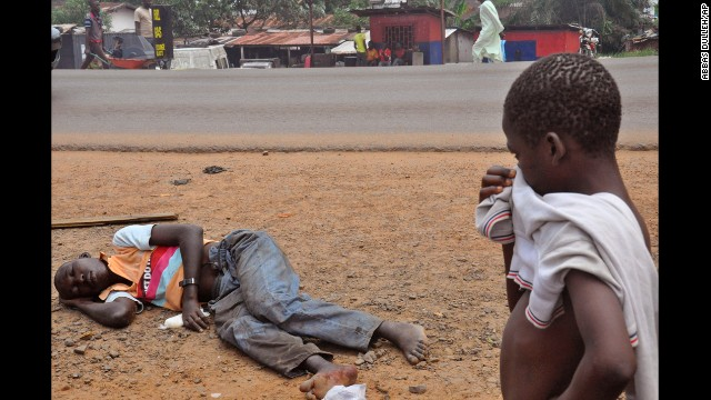 A child stops on a Monrovia street Friday, September 12, to look at a man who is suspected of suffering from Ebola.