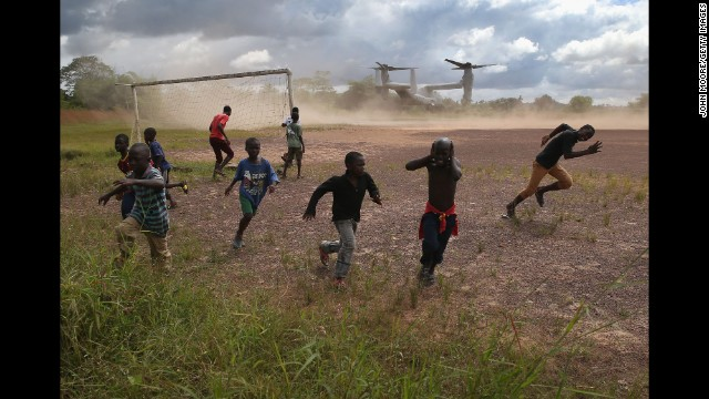 Boys run from blowing dust as a U.S. military aircraft leaves the construction site of an Ebola treatment center in Tubmanburg, Liberia, on Wednesday, October 15.
