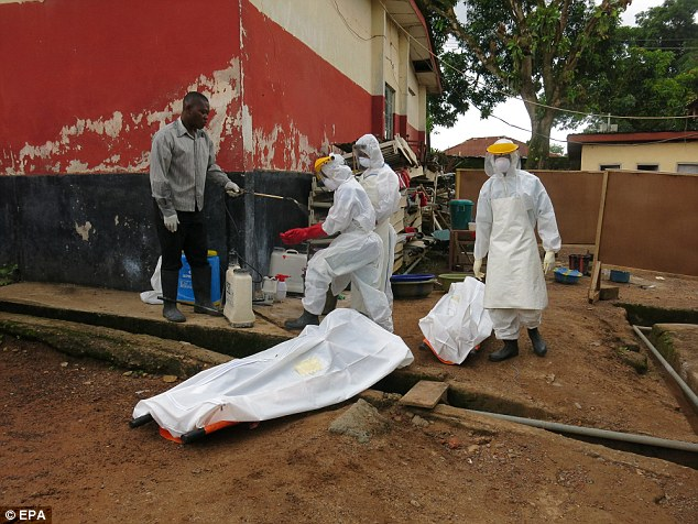 Health workers working with the bodies of Ebola victims at Kenema Hospital in Sierra Leone