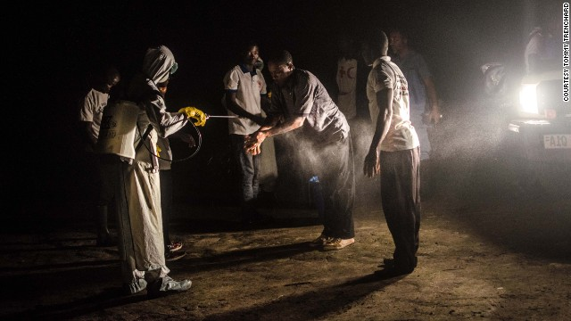 Red Cross volunteers disinfect each other with chlorine after removing the body of an Ebola victim from a house in Pendembu on July 18.