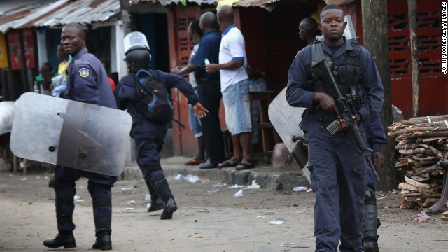 Liberian police depart after firing shots in the air while trying to protect an Ebola burial team in the West Point slum of Monrovia on August 16. A crowd of several hundred local residents reportedly drove away the burial team and their police escort. The mob then forced open an Ebola isolation ward and took patients out, saying the Ebola epidemic is a hoax.