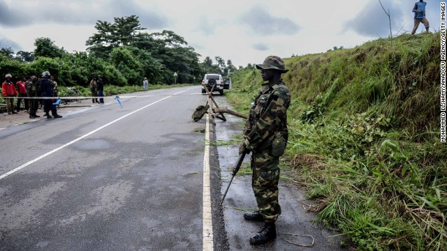 A guard stands at a checkpoint Saturday, August 23, between the quarantined cities of Kenema and Kailahun in Sierra Leone.