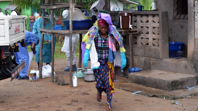 A woman in Monrovia carries the belongings of her husband, who died after he was infected by the Ebola virus.