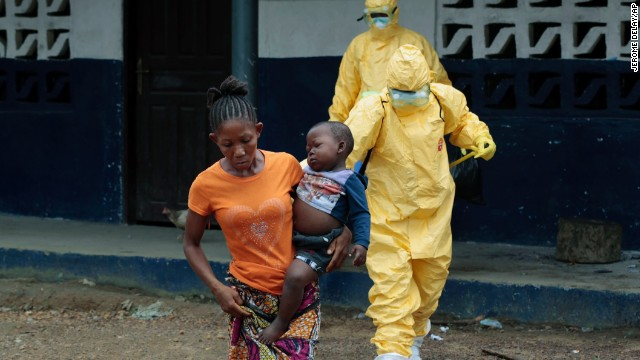 Marie Nyan, whose mother died of Ebola, carries her 2-year-old son, Nathaniel Edward, to an ambulance in the Liberian village of Freeman Reserve on Tuesday, September 30.