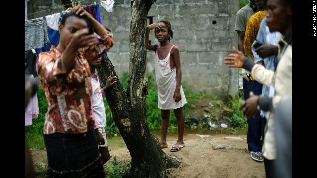 A girl cries as community activists approach her outside her Monrovia home on Thursday, October 2, a day after her mother was taken to an Ebola ward.