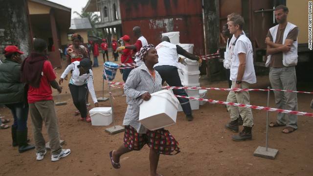 Residents of an Ebola-affected township take home kits distributed by Doctors Without Borders on Saturday, October 4, in New Kru Town, Liberia. The kits, which include buckets, soap, gloves, anti-contamination gowns, plastic bags, a spray bottle and masks, are meant to give people some level of protection if a family member becomes sick.