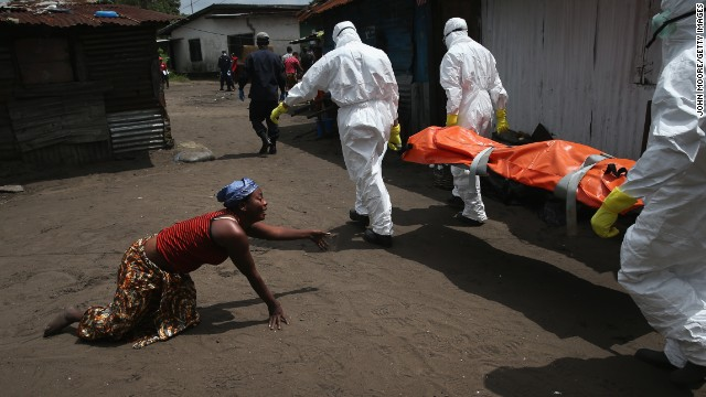 A woman crawls toward the body of her sister as a burial team takes her away for cremation Friday, October 10, in Monrovia. The sister had died from Ebola earlier in the morning while trying to walk to a treatment center, according to her relatives.