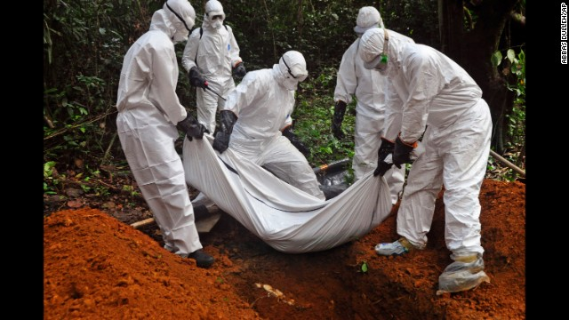 Health workers bury a body on the outskirts of Monrovia on Monday, October 20.