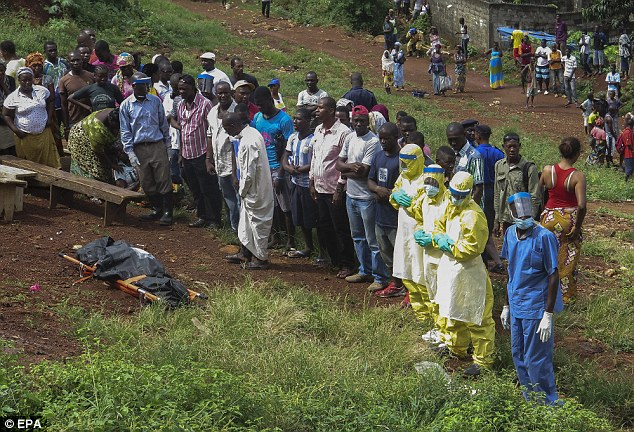 Prayers are said for a victim of Ebola  in Freetown, Sierra Leone as healthcare workers prepare to remove the body from public